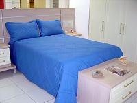 Foto de uma cama com edredon e travesseiros
